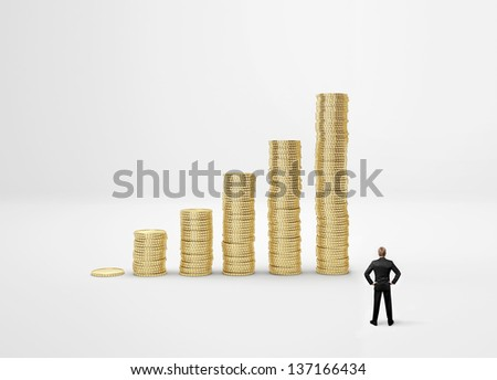 Businessman looking at coin diagram - stock photo