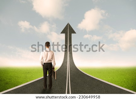 Businessman looking at 3d road upgoing arrow concept - stock photo