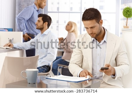Businessman looking at diagrams, holding mobilephone, working in busy office. - stock photo