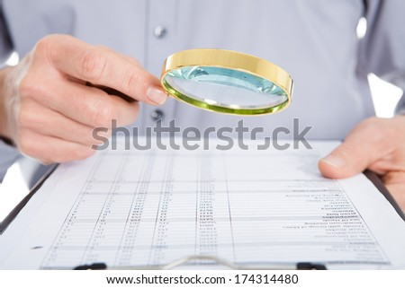 Businessman Looking At Document Through Magnifying Glass On White Background - stock photo