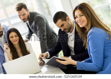 Businessman looking at documents while other business people talking