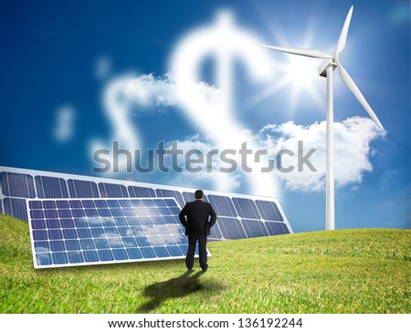 Businessman looking at dollar signs made of clouds in a field with solar panels and wind turbine - stock photo