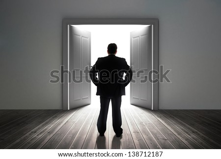 Businessman looking at door showing bright light in dull grey room