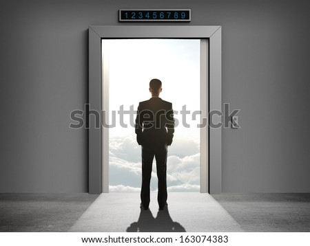 businessman looking at elevator to cloud