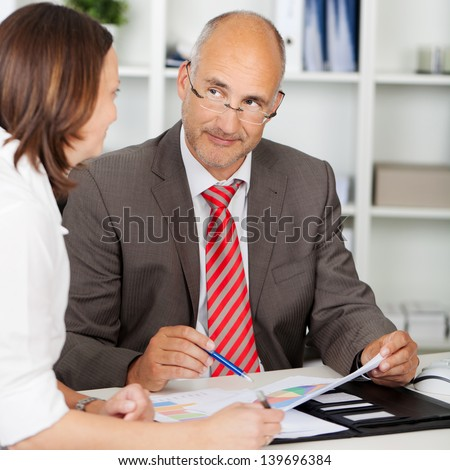 businessman looking at female colleague in meeting - stock photo