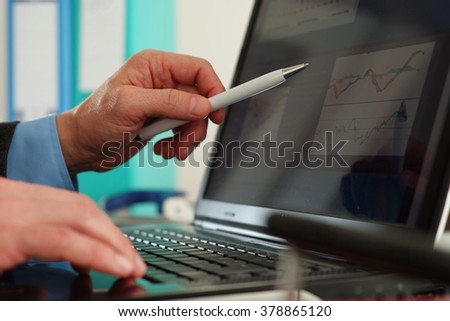 Businessman looking at financial data on laptop screen