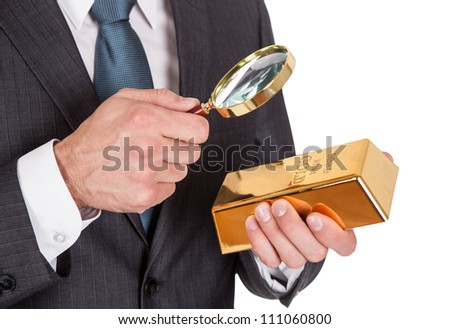 Businessman looking at gold bar through loupe. Isolated on white - stock photo