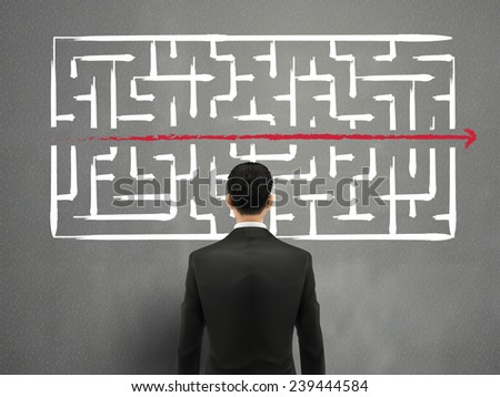 businessman looking at hand drawn maze over grey  - stock photo