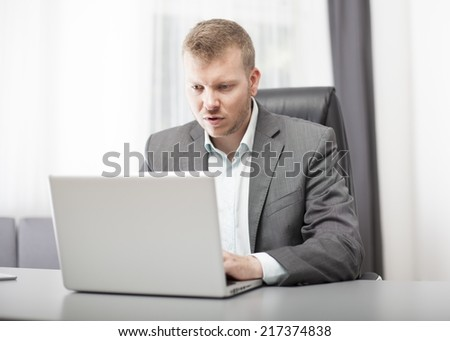 Businessman looking at his laptop in disbelief with a puzzled shocked expression as he digests the information on the screen - stock photo