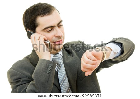 Businessman looking at his watch and talking on the phone on a white background.