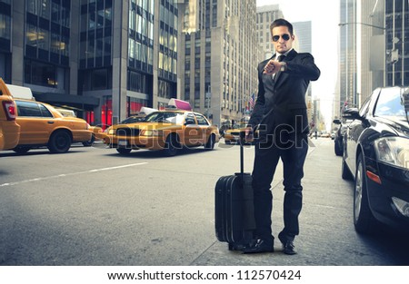 Businessman looking at his watch in New York - stock photo