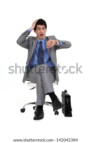 Businessman looking at his watch in shock - stock photo