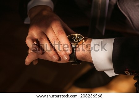 Businessman looking at his watch punctuality - stock photo