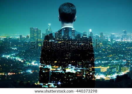 Businessman looking at illuminated night city. Double exposure - stock photo