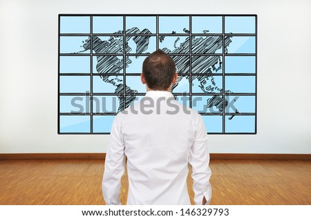businessman looking at map of world on flat panels
