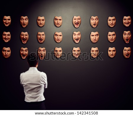 businessman looking at mask and selecting his mood - stock photo