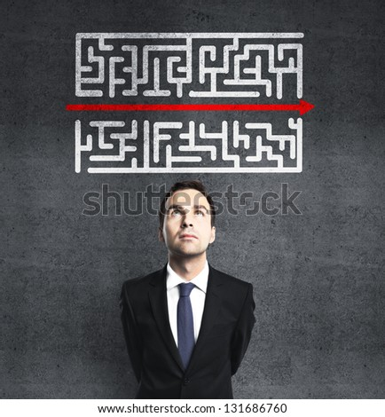 businessman looking at maze with red arrow - stock photo