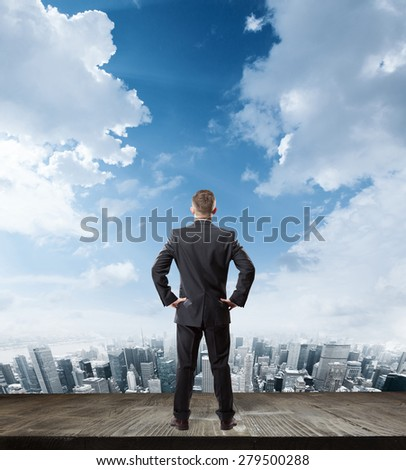 businessman looking at modern city building with wooden floor in front