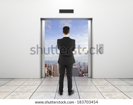 businessman  looking at modern elevator with opened door to city