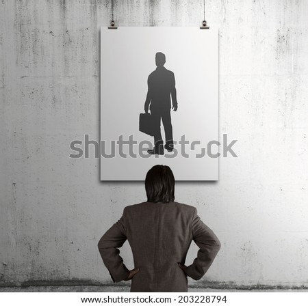 businessman looking at people icon on art frame on the wall as human resources concept
