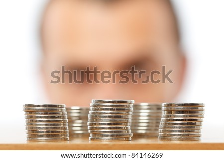 Businessman looking at piles of pennies, financial crisis or savings concept - stock photo