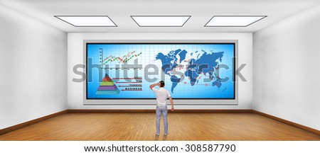 businessman looking at plasma tv with chart and international flights scheme - stock photo