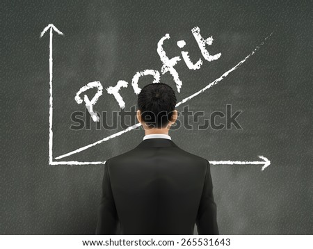 businessman looking at profit graph on wall