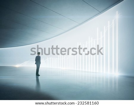 Businessman looking at shining chart on the wall - stock photo