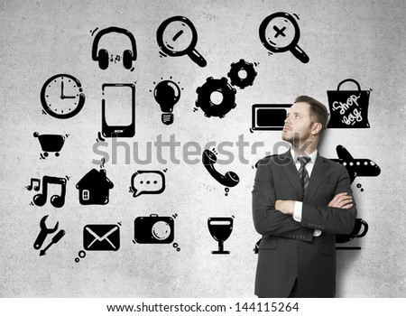 businessman looking at social icons drawing on concrete wall - stock photo
