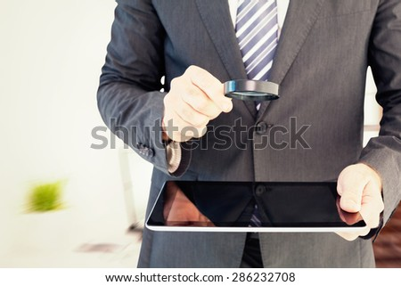 Businessman looking at tablet with magnifying glass against laptop on desk with glasses and notepad - stock photo