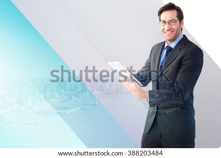 Businessman looking at the camera while using his tablet against city by the sea - stock photo