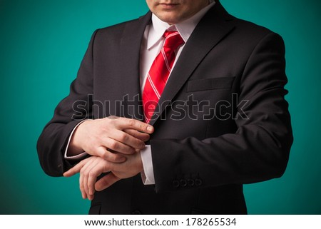 Businessman looking at the time on his imaginary wrist watch against green background.  - stock photo