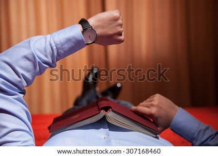 Businessman looking at the wristwatch and lying on the bed with book, closeup shot - stock photo