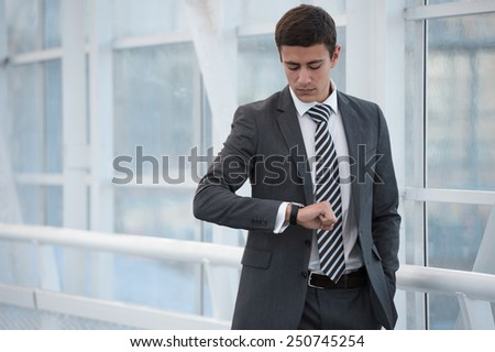 Businessman looking at watches while walking outside modern building - stock photo
