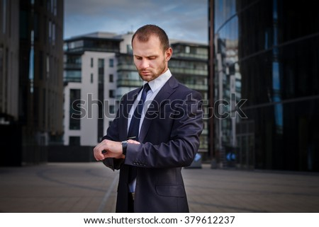 Businessman looking at watches while walking outside modern office building