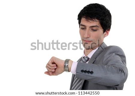 Businessman looking at wrist watch - stock photo