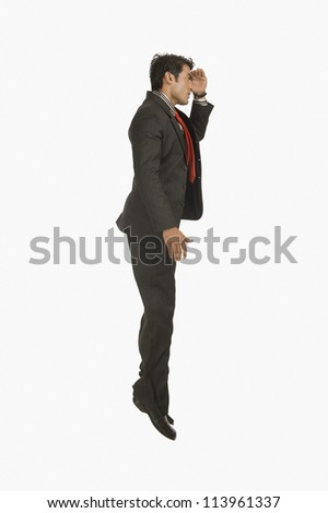 Businessman looking away with shielding his eyes