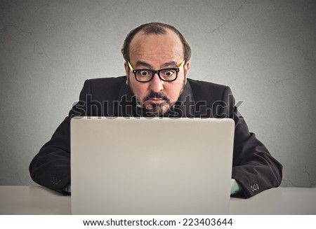 businessman looking concentrated on computer screen trying to solve a problem on his pc sitting at desk on grey wall office background. Human face expression. Internet privacy cyber crime concept - stock photo