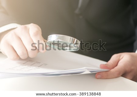 businessman  looking documents through the magnifying glass - stock photo