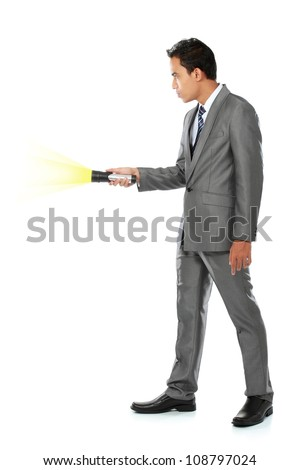businessman looking for something with flashlight