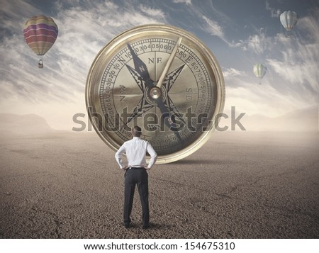 Businessman looking for the destination of business compass - stock photo