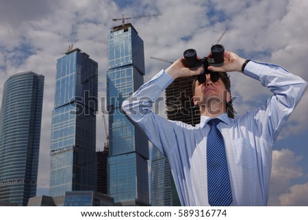 Businessman looking forward through binoculars against skyscrapers under construction