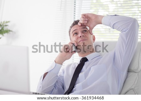 Businessman looking frustrated at the office .He is working on his laptop and talking on the phone. - stock photo