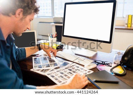 Businessman looking his photo in office