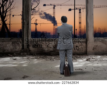Businessman looking industrial place at sunset