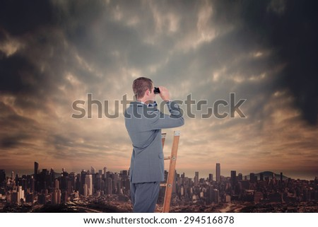 Businessman looking on a ladder against dusty path leading to large city - stock photo