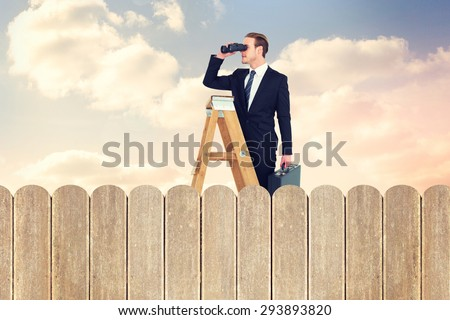 Businessman looking on a ladder against purple sky over fence - stock photo