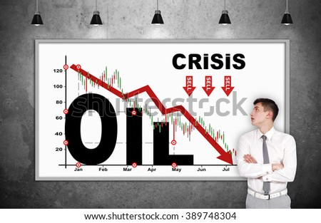 businessman looking on oil crisis chart on whiteboard - stock photo