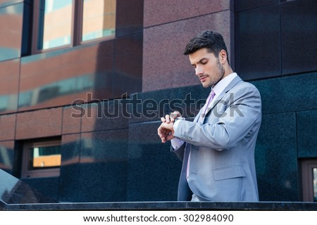 Businessman looking on wrist watch outdoors near office building - stock photo