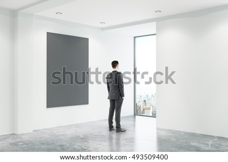 Businessman looking out of window in empty concrete office interior with blank chalkboard city view. Mock up, 3D Rendering